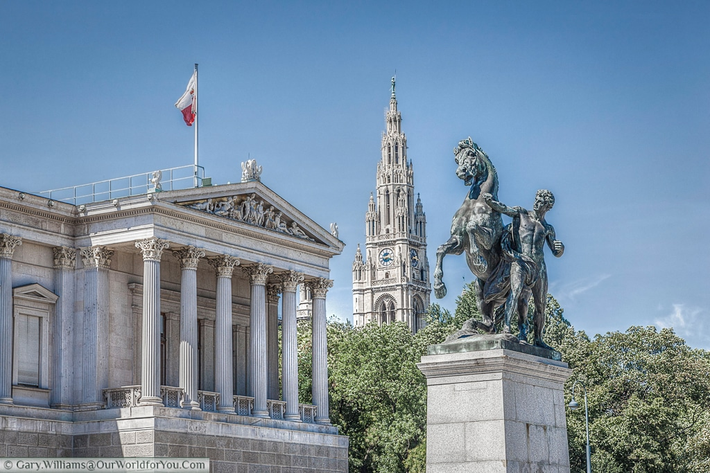The Horse Tamer statue is one of a pair flanking the entrance to the parliament buildings.  The Rathaus clock tower features in the background, Vienna, Austria