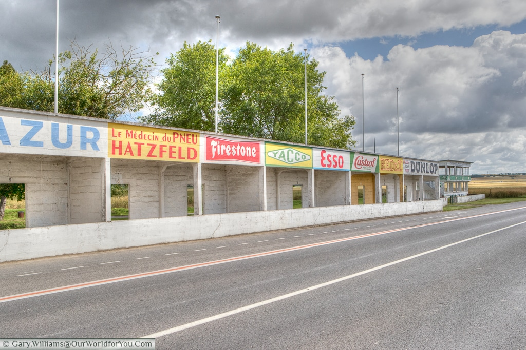 The bright coloured advertising hoardings above the pits of the Circuit Reims-Gueux, Reims, France