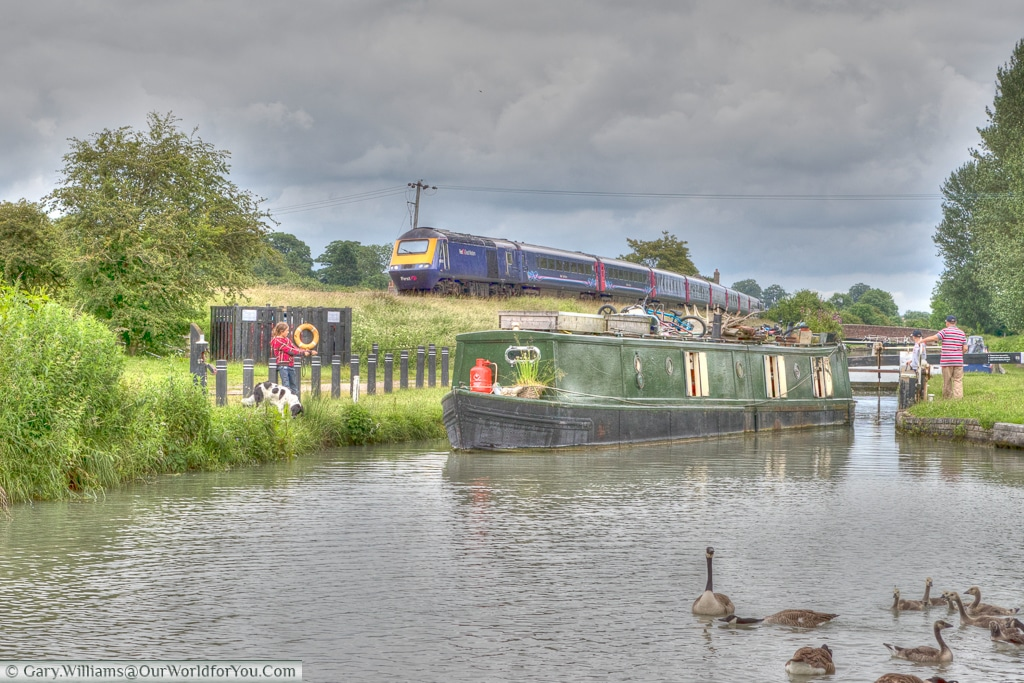 The train line follows the canal and the two modes of transport appear in the same shot on the Kennet & Avon Canal, England, United Kingdom
