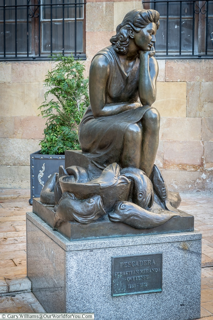 The beautiful 'Pescadera' figure depicted in this sculpture is deep in thought with fish lapping at her feet, Oviedo, Spain