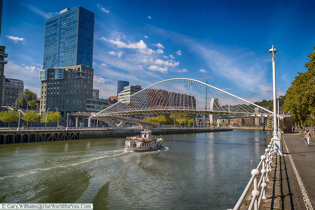 A boat motors under the Zubizuri or 'White Bridge', Bilbao, Spain